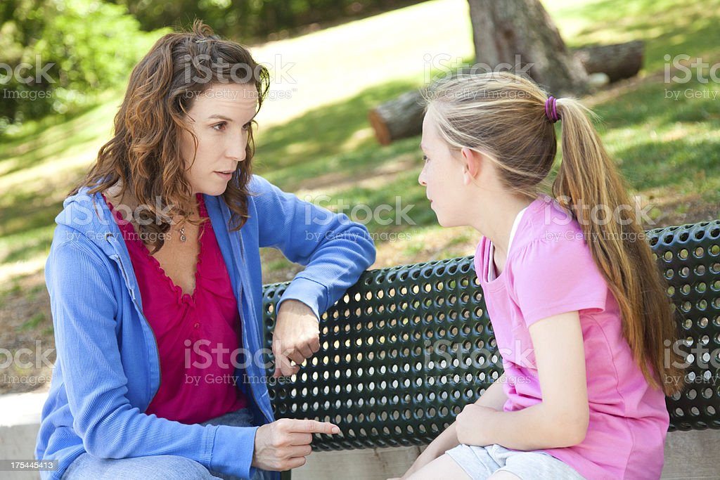 Concerned mother talking with her daughter royalty-free stock photo