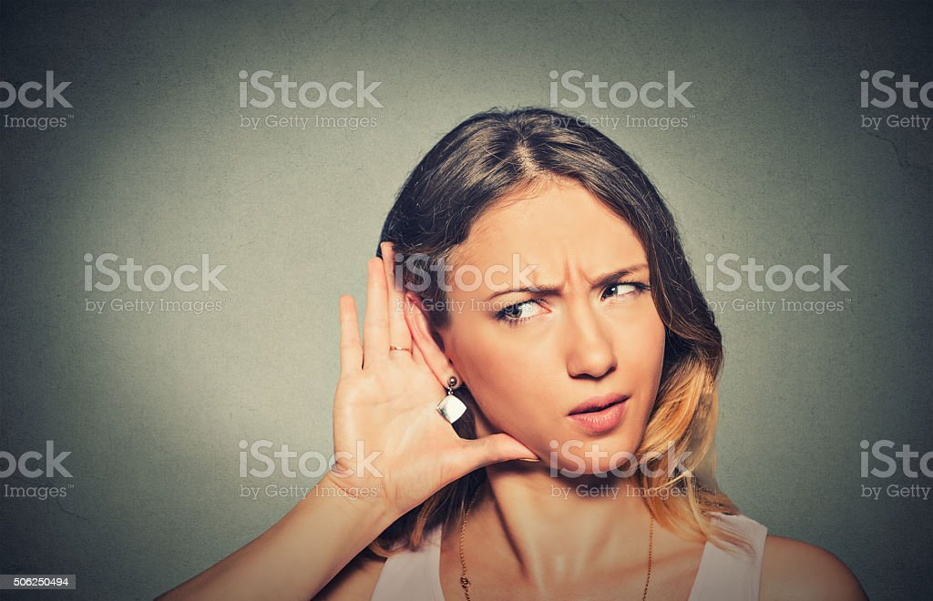 concerned nosy woman hand to ear gesture carefully listening stock photo