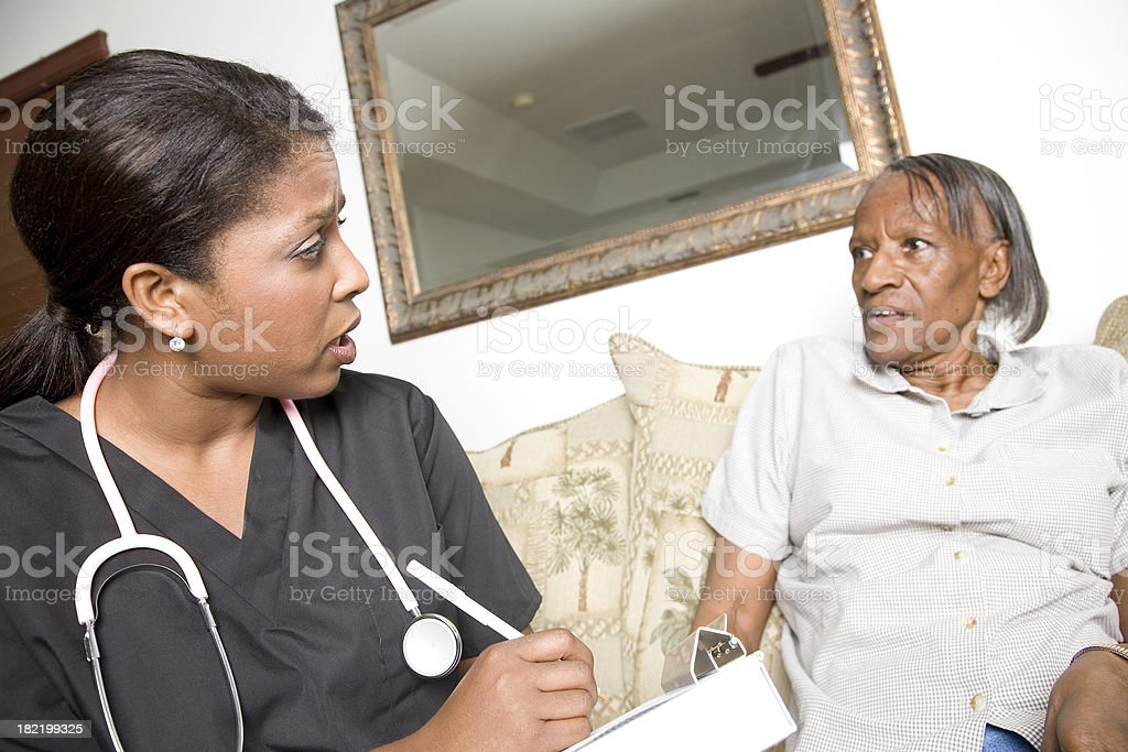 Concerned Nurse Performing Check Up With Her Elderly Patient royalty-free stock photo