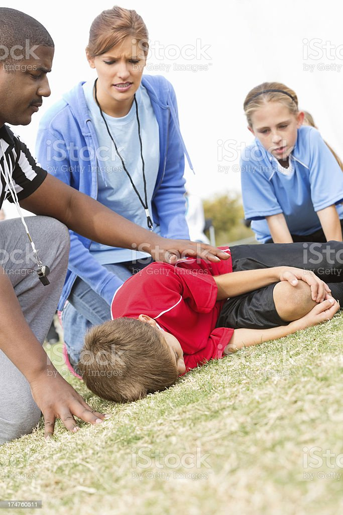 Concerned referee and coach with injured soccer player royalty-free stock photo