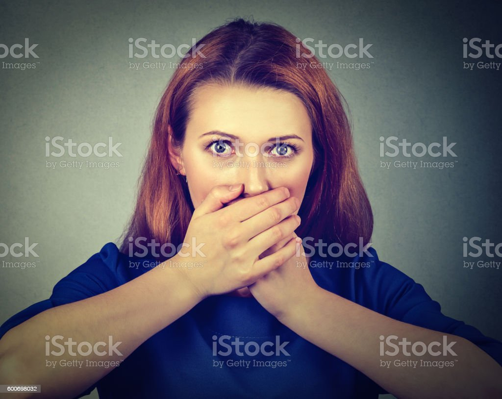 Concerned scared woman covering her mouth with hands stock photo
