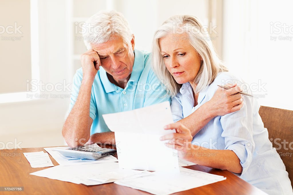 Concerned senior couple calculating home finances at a table royalty-free stock photo