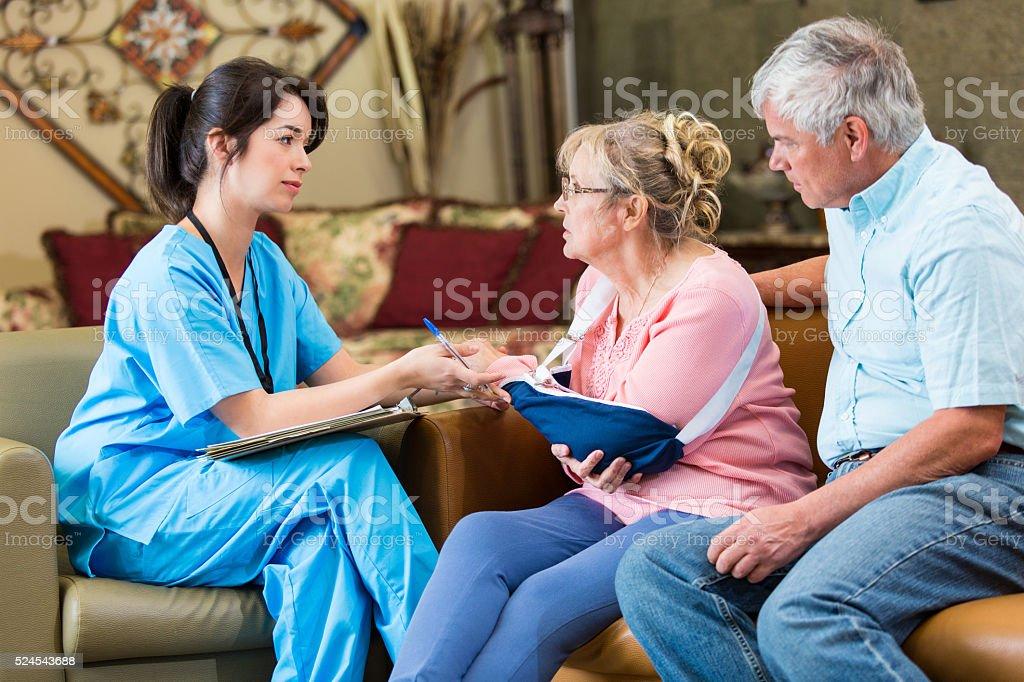 Concerned senior patient talks with home healthcare nurse stock photo