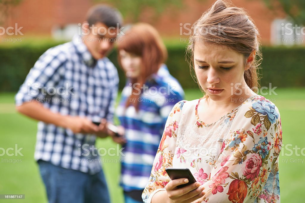A concerned teenage girl being bullied by text message stock photo