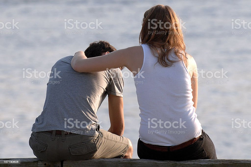 concerned woman comforts frustrated man at a beach stock photo
