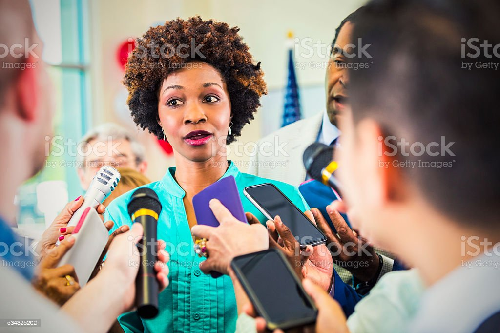 Concerned woman confronted by journalists stock photo