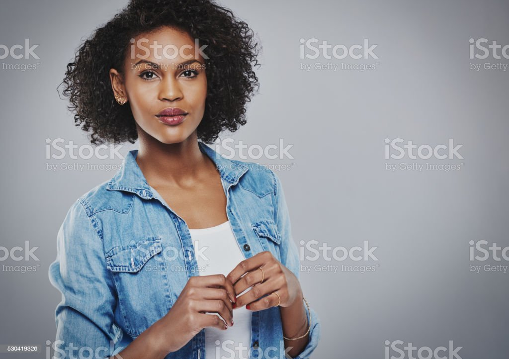 Concerned woman in blue holds hands together stock photo