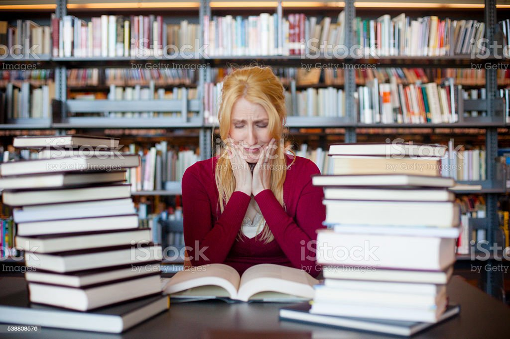 Concerned Woman Studying in the Library stock photo
