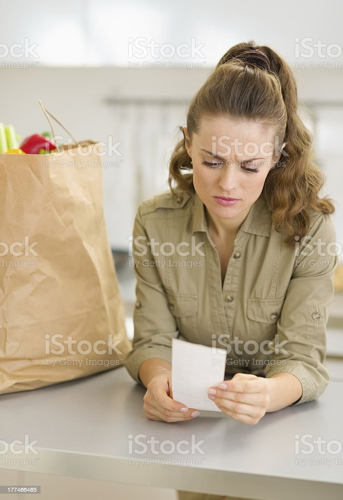 Concerned young housewife examines check after shopping royalty-free stock photo