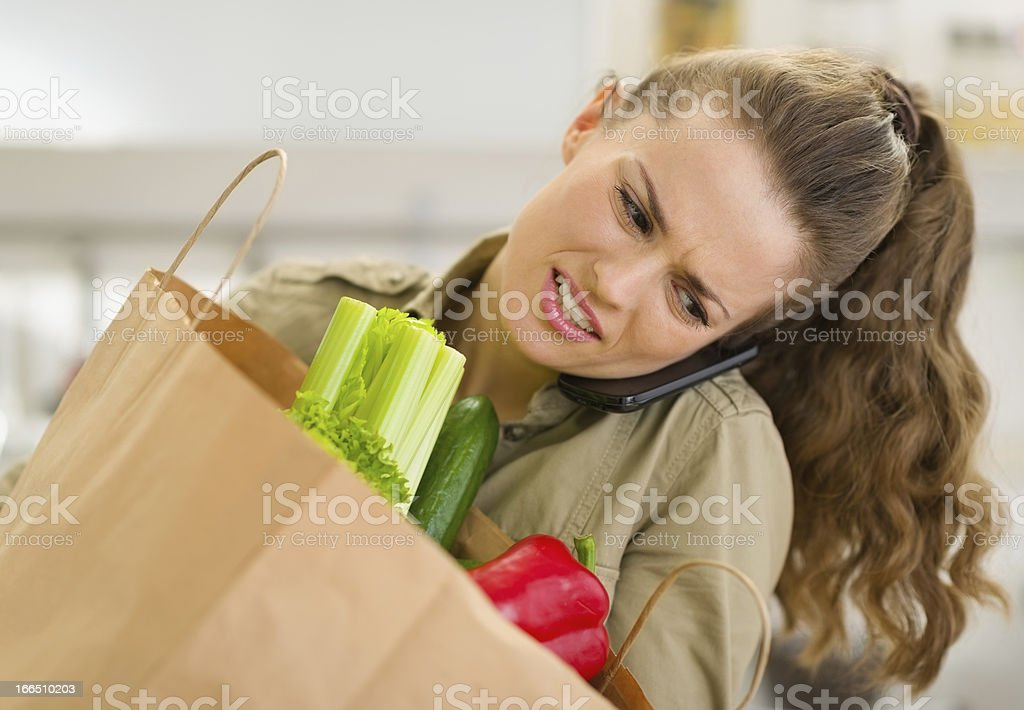 Concerned young housewife with big shopping bag talking mobile phone royalty-free stock photo