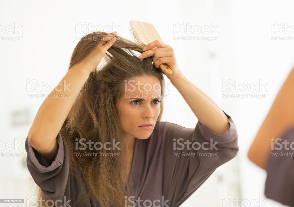 concerned young woman combing hair in bathroom stock photo