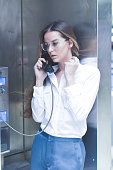 Concerned Young Woman Talking on a Payphone