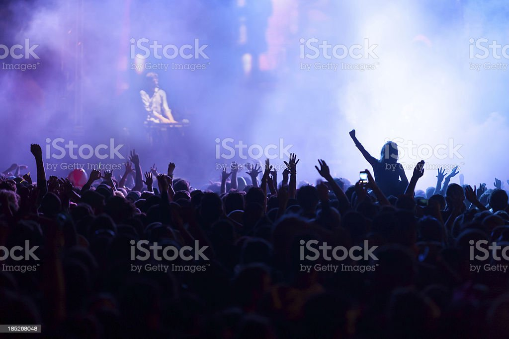 A back lit crowd with arms up at a music concert with a...