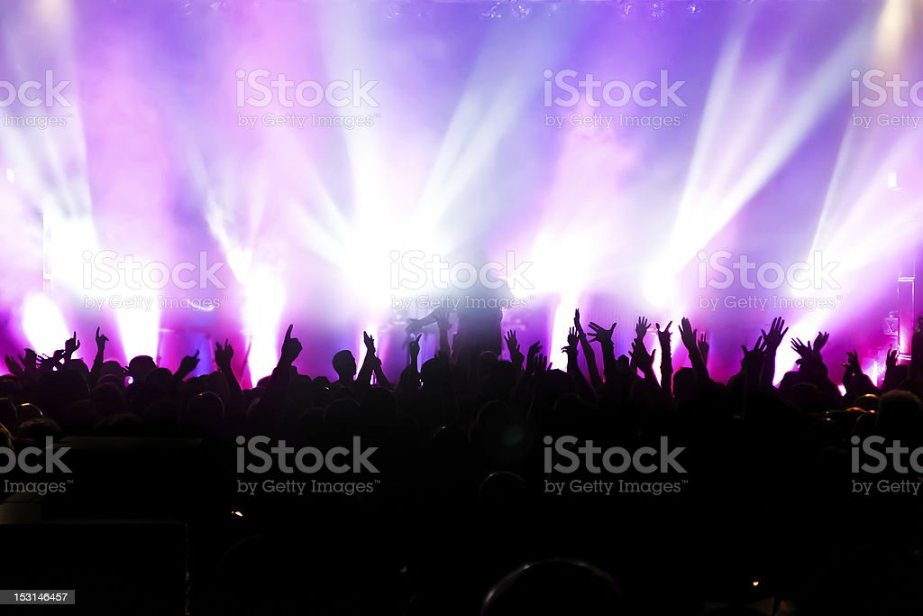 Concert crowd in front of purple spotlights royalty-free stock photo