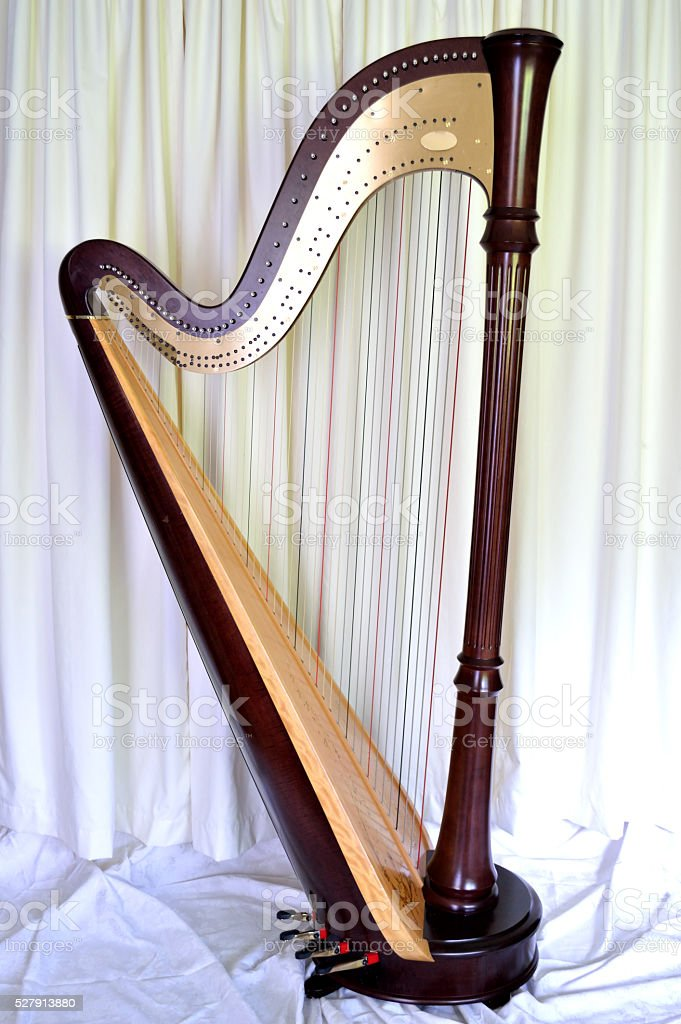 Concert grand pedal harp against white curtains stock photo