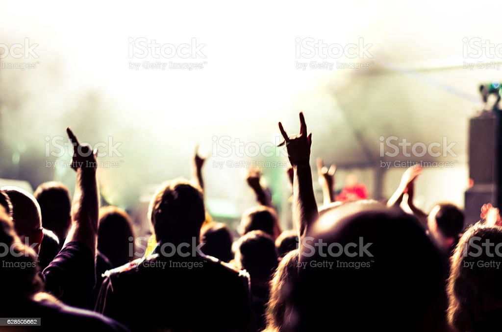 unrecognisable spectators in a concert with hands up