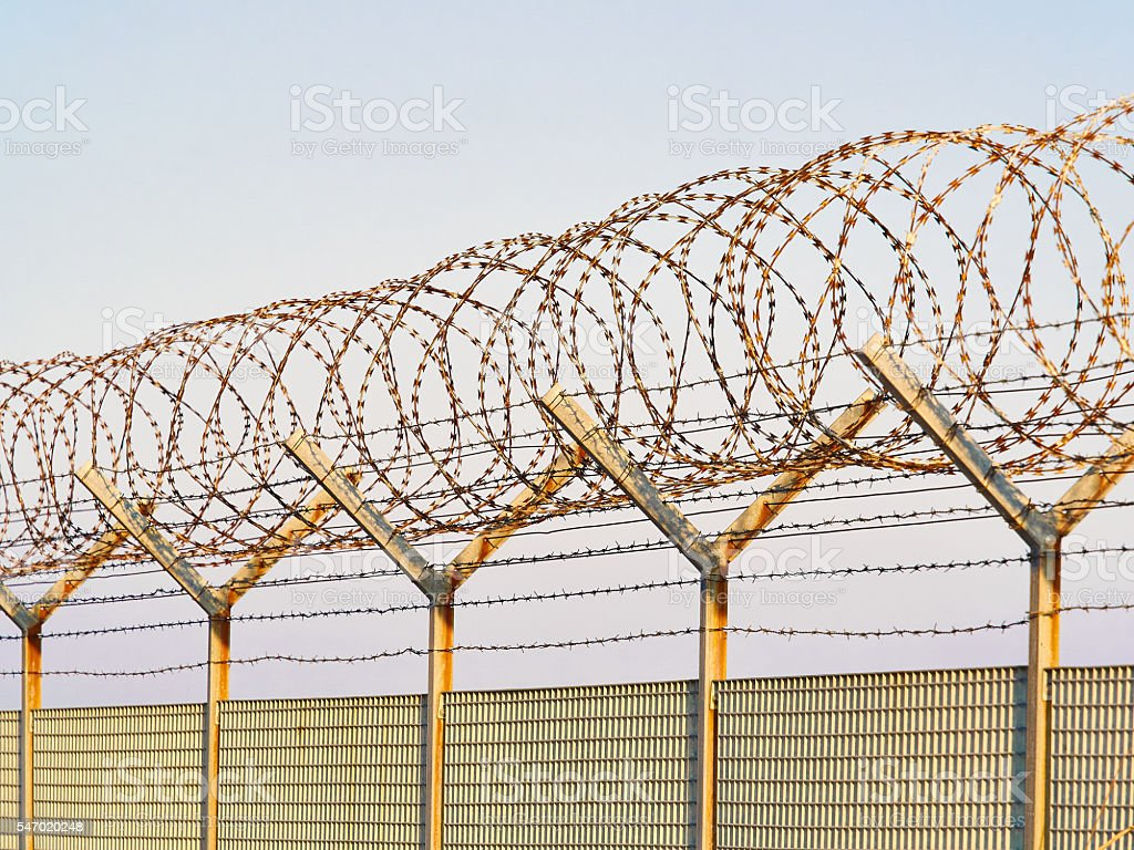 Concertina razor wire and barbed wire on a metal fence stock photo