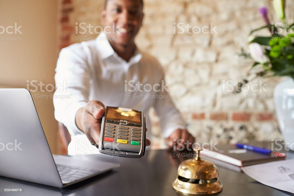 Concierge at hotel reception holds credit card reader to camera stock photo