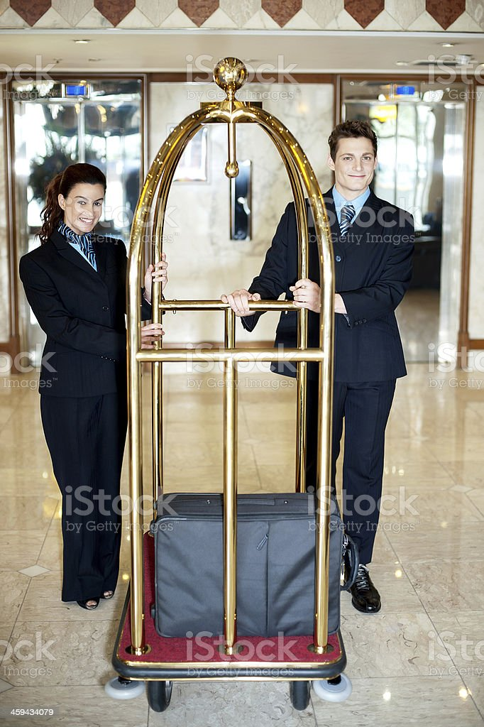 Concierge colleagues holding baggage cart stock photo