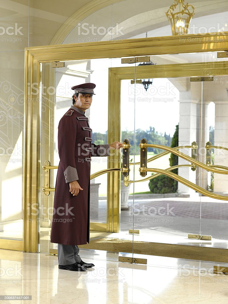 Concierge holding door in hotel foyer, portrait stock photo