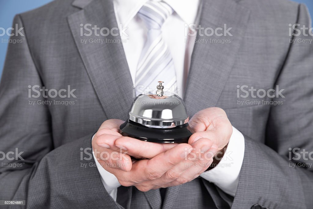 Concierge holding service bell stock photo