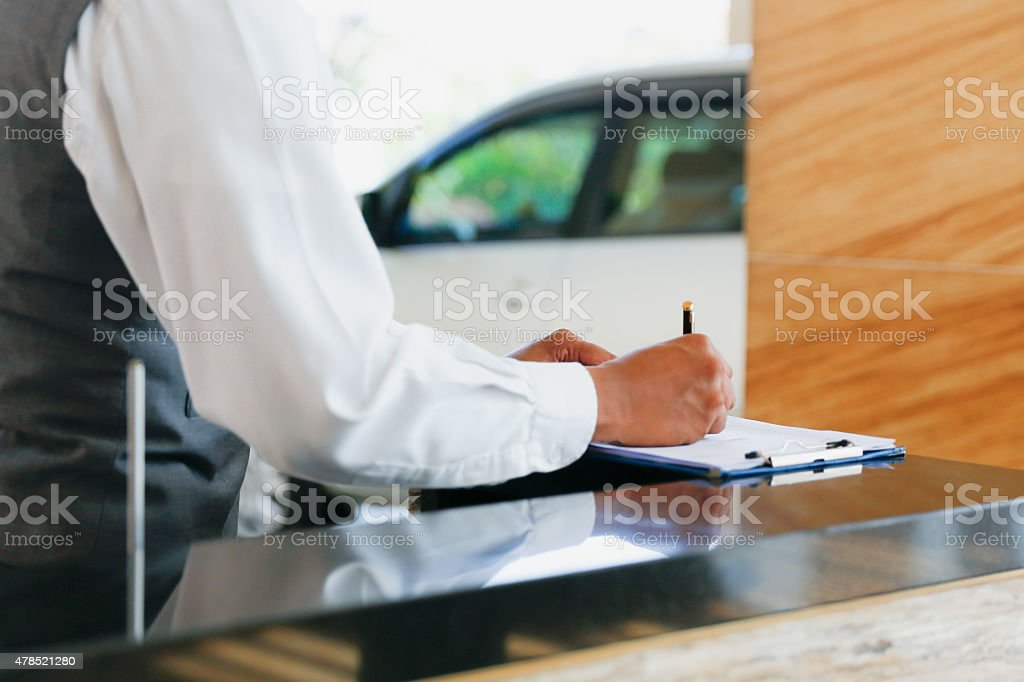 Concierge of luxury hotel writing a note stock photo