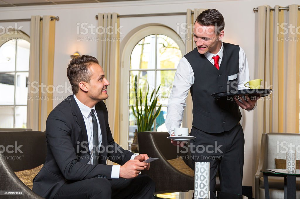 Concierge serving guest at hotel a cup of coffee stock photo