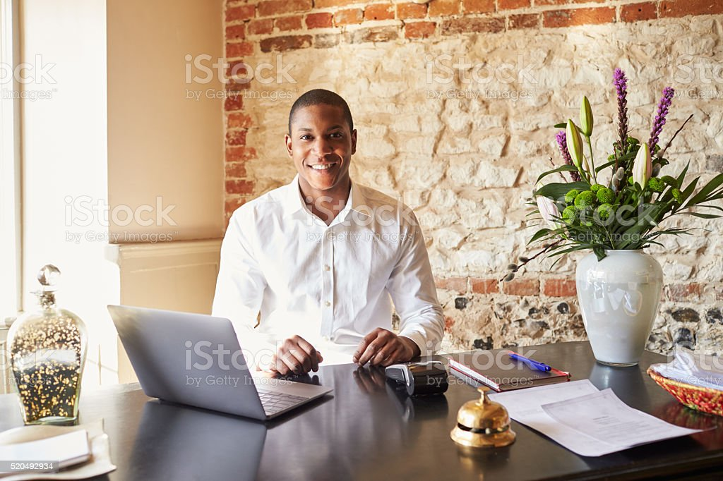 Concierge working at the check in desk of a boutique stock photo