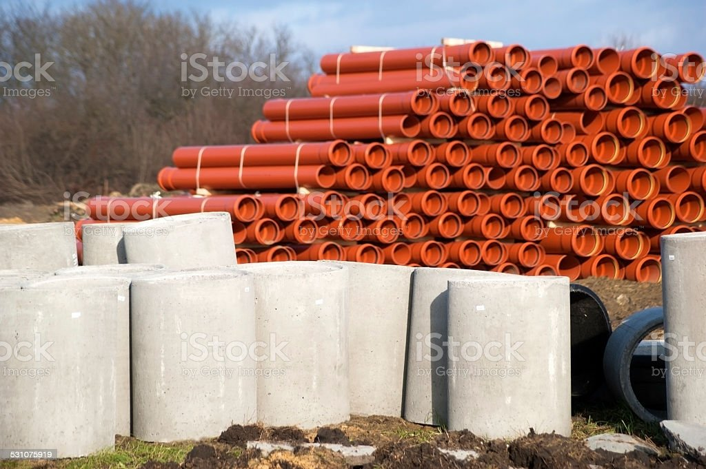 Concret and orange PVC drainage pipes in road construction stock photo