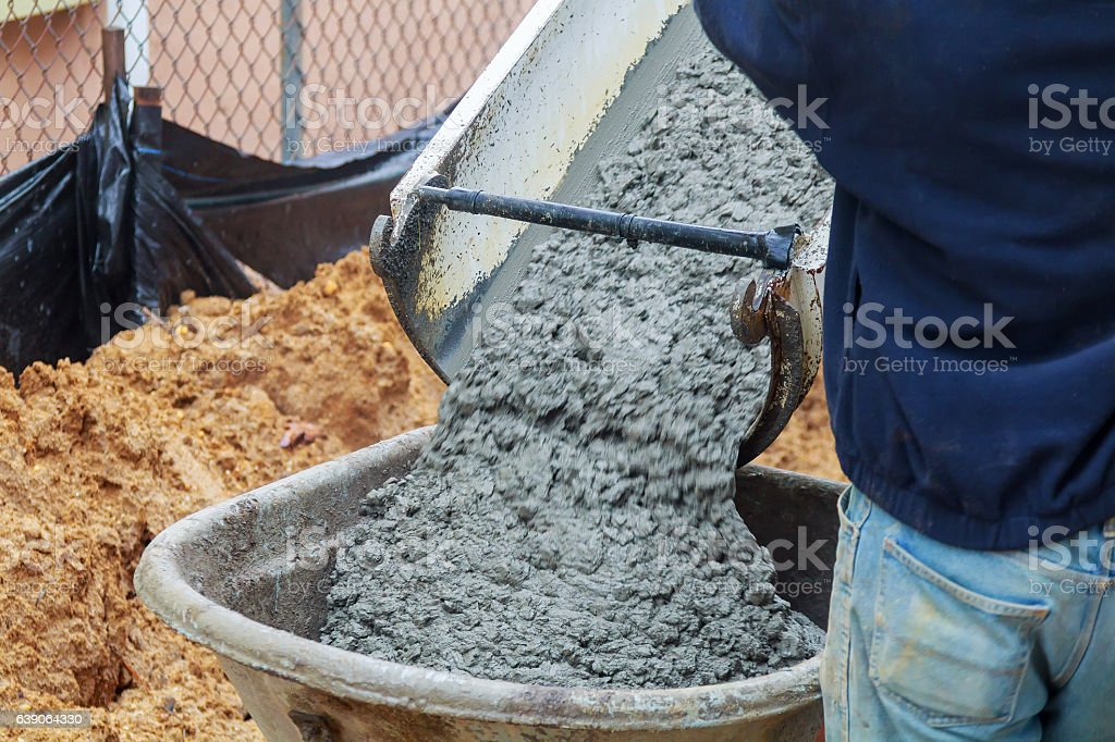 Concrete being poured from a truck into   pump stock photo