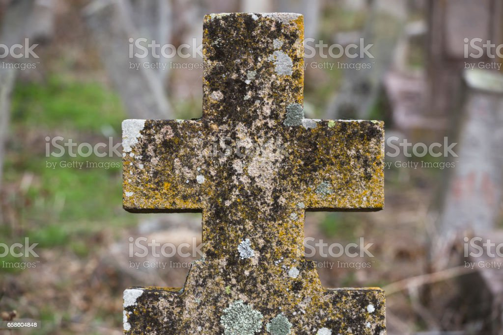 Concrete Christian tombstone covered with lichen on old graveyard stock photo