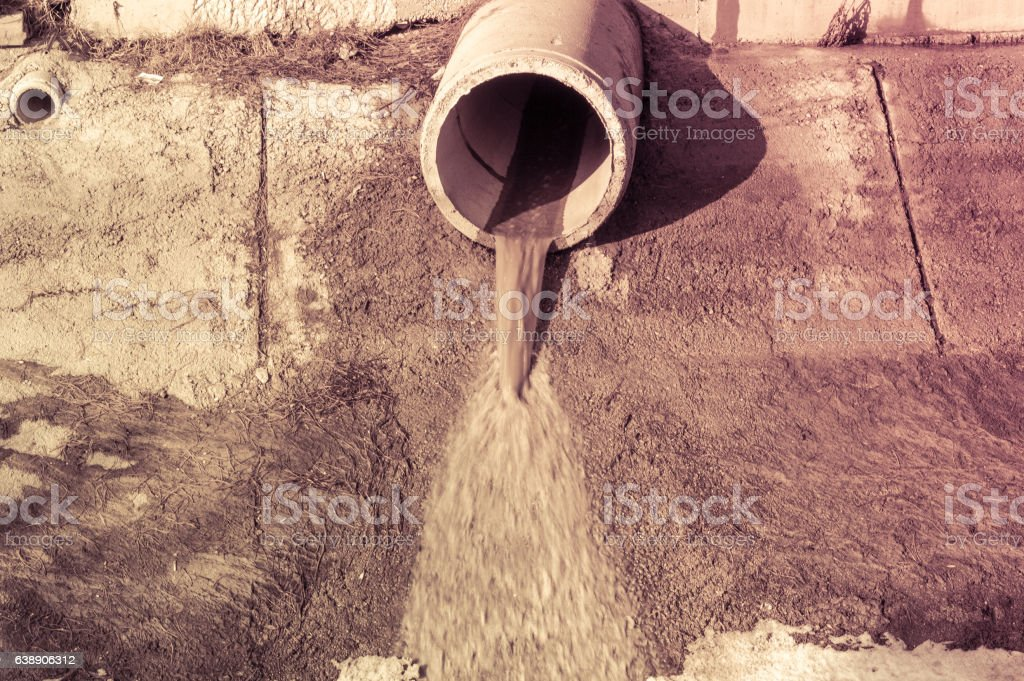 Concrete circular pipe discharging water to a canal stock photo