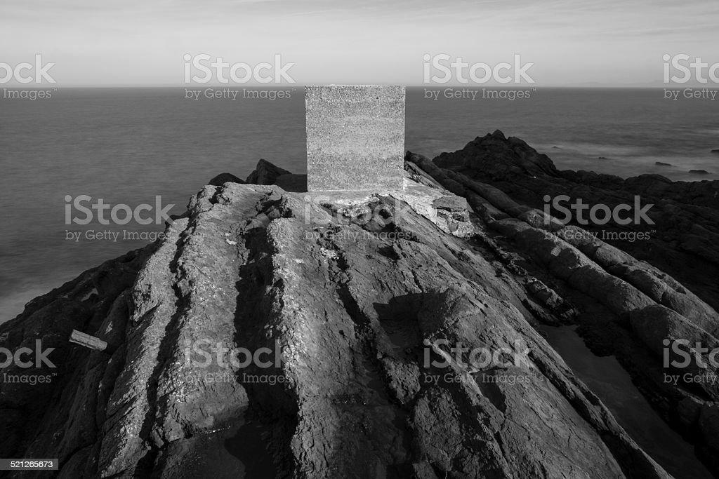 Concrete cube on the rocks stock photo
