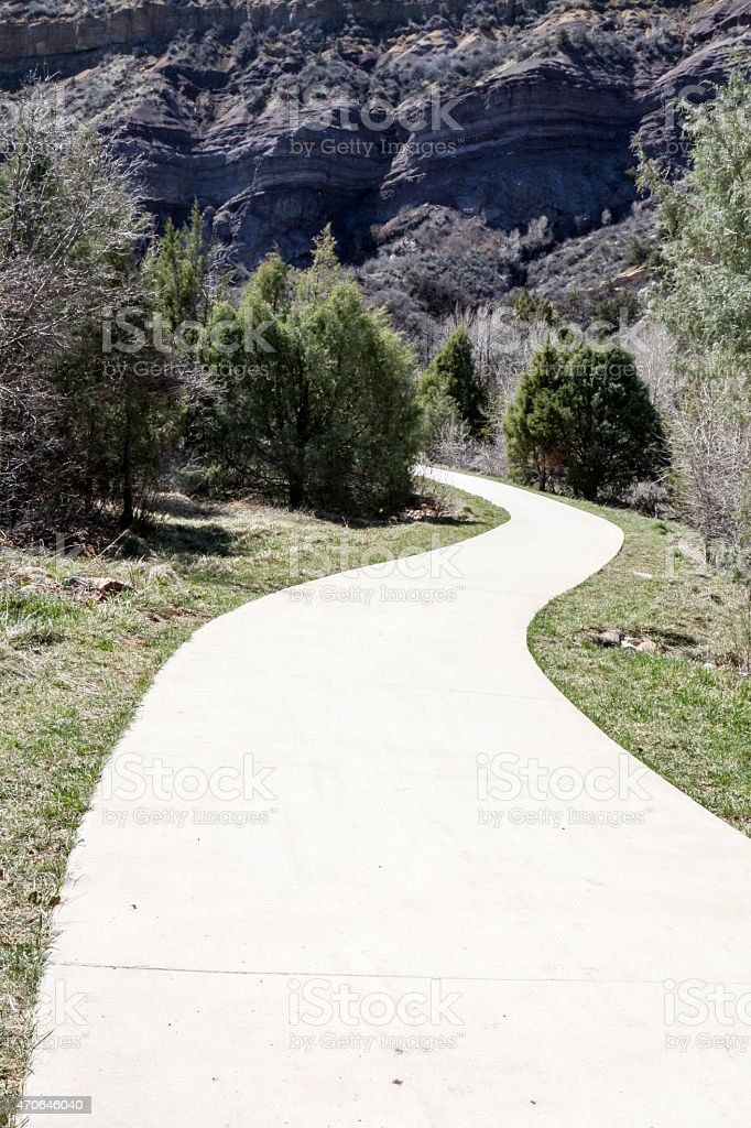 Concrete footpath curving into trees with sheer rock cliff stock photo