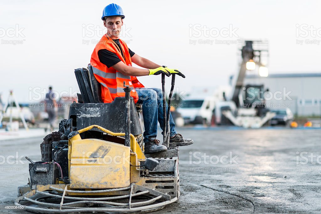 Concrete leveling with power trowel stock photo