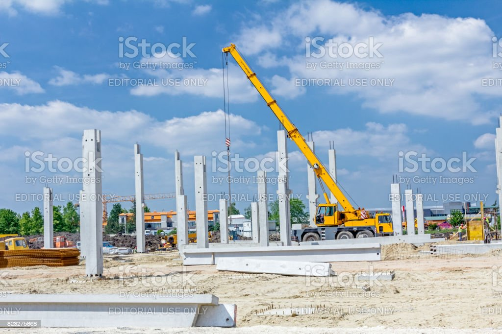 Concrete pillars of new edifice with a beautiful sky are placed on sandy ground stock photo