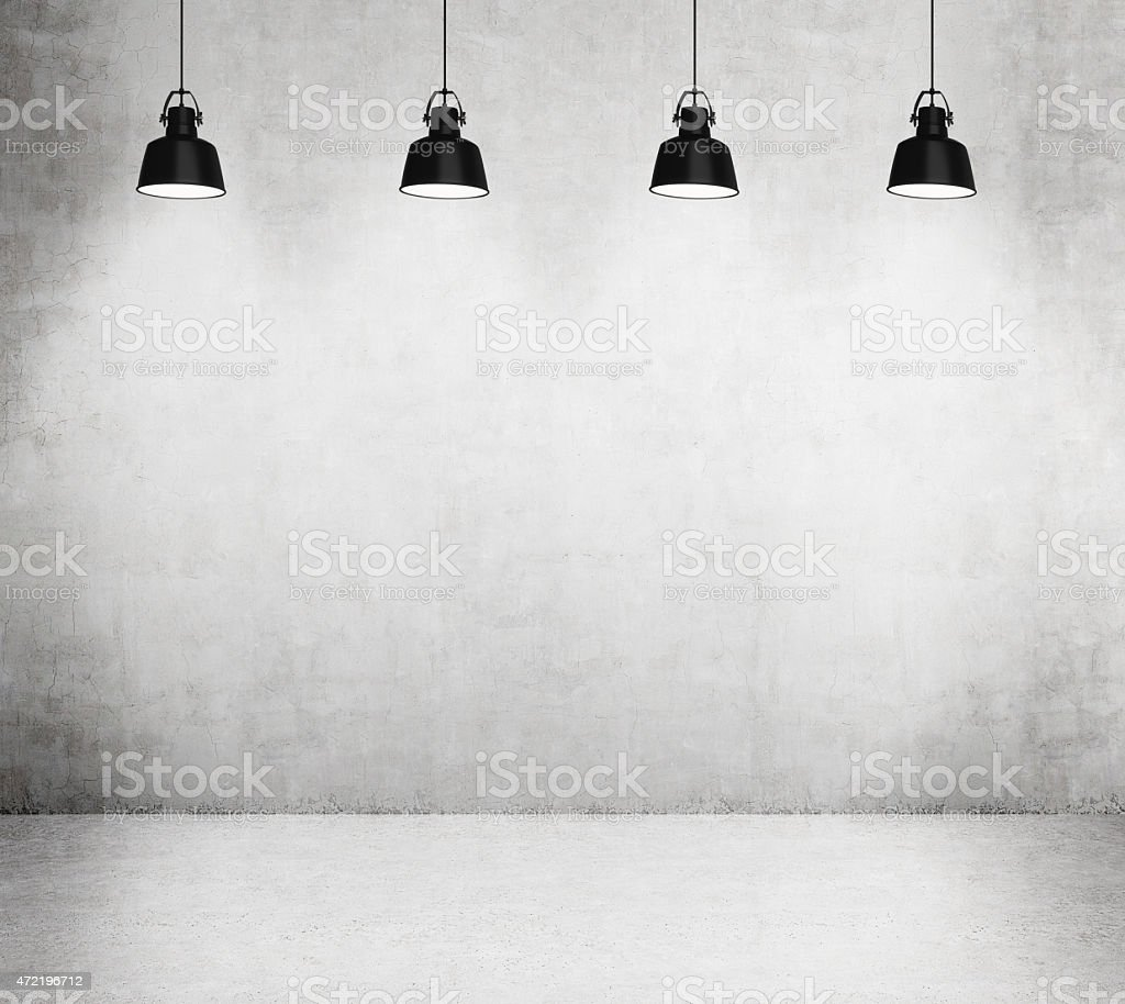 Concrete room with four black lamps. stock photo