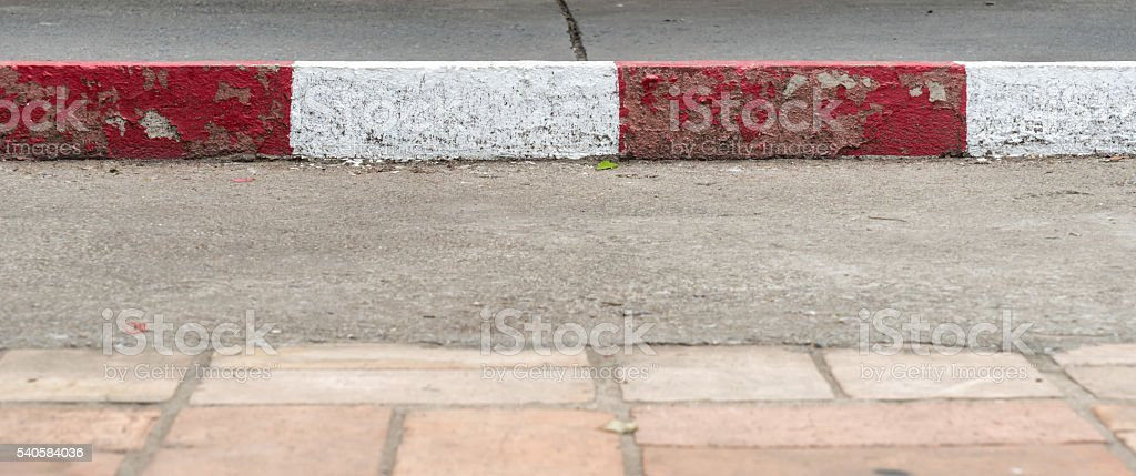 Concrete sidewalk with red and white stock photo
