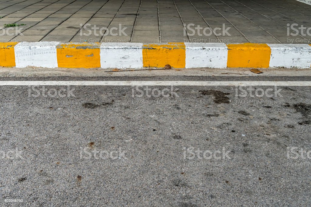 Concrete sidewalk with yellow and white stock photo