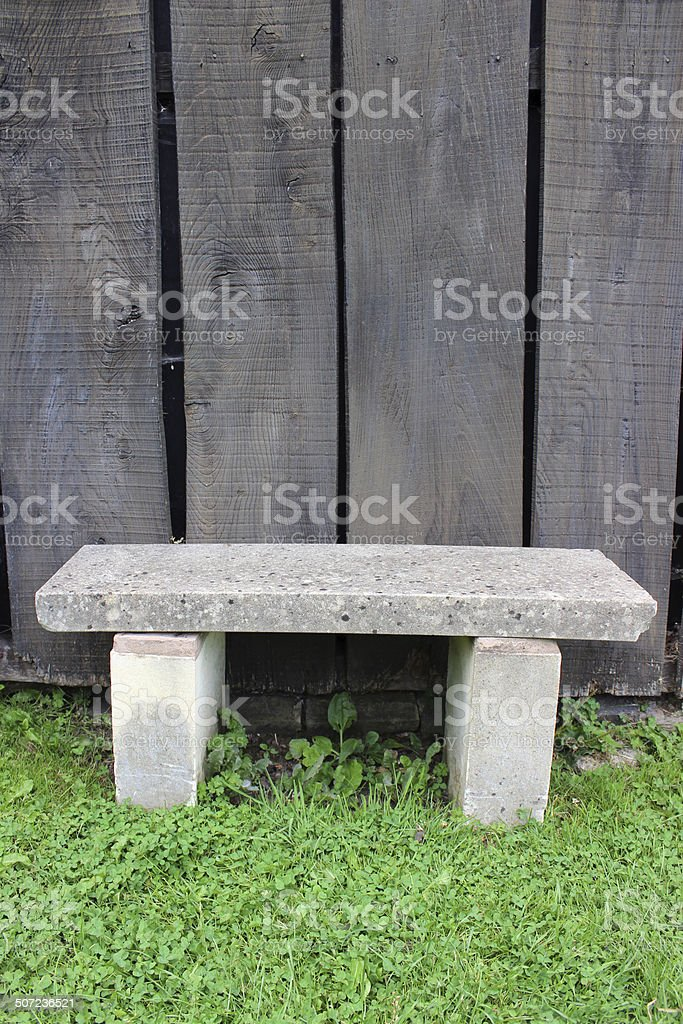 Concrete Stone Garden Bench On Green Lawn, Wooden Fence Slats Royalty Free  Stock Photo