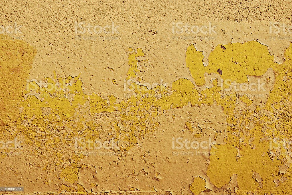 Concrete wall painted yellow with peeling paint royalty-free stock photo