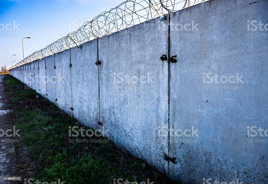 Concrete wall with barbed wire on top. stock photo