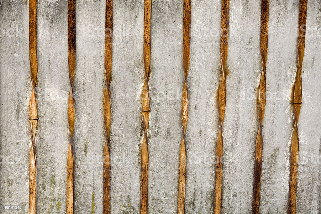 Concrete wall with twisted rusty metal rails; background royalty-free stock photo