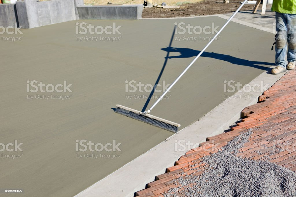 Concrete Worker Brushing Texture into a New Patio Slab stock photo