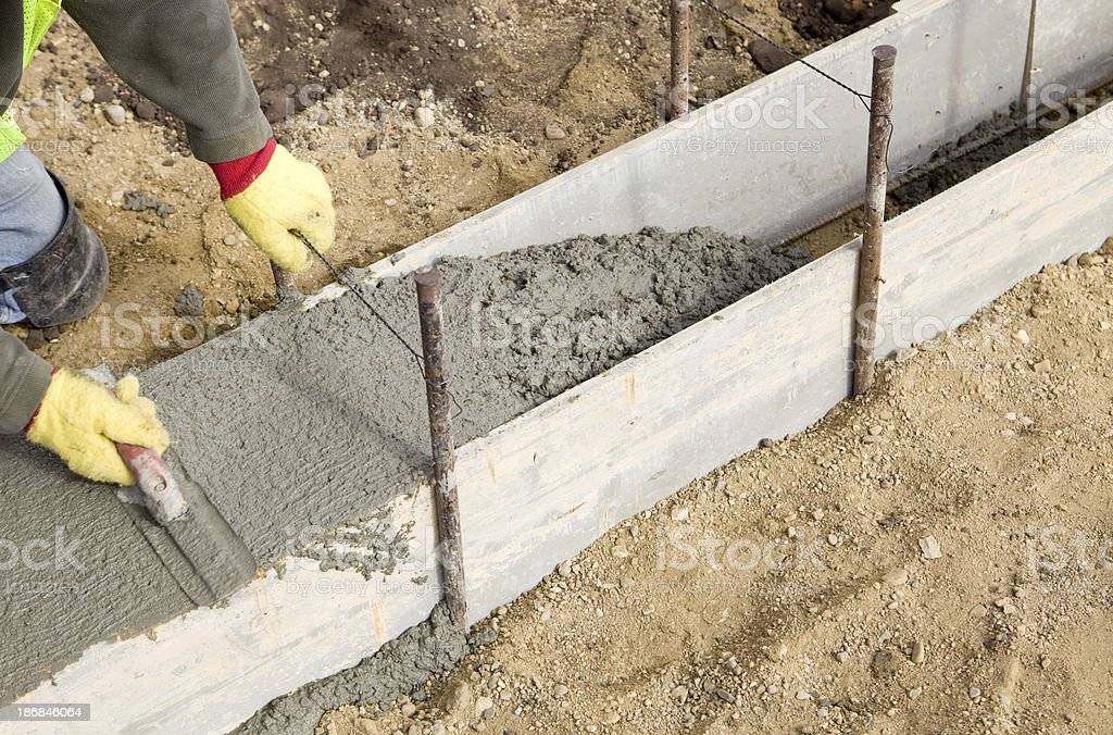 Concrete Worker Troweling a New Footing stock photo