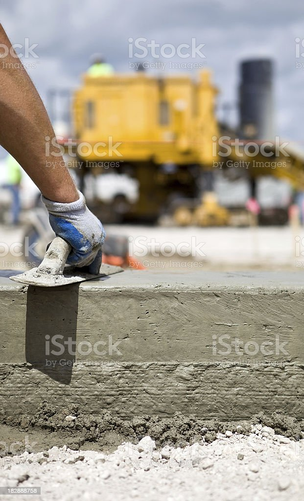 Concrete Worker Troweling  Curb with Slipform Paver in the Background stock photo