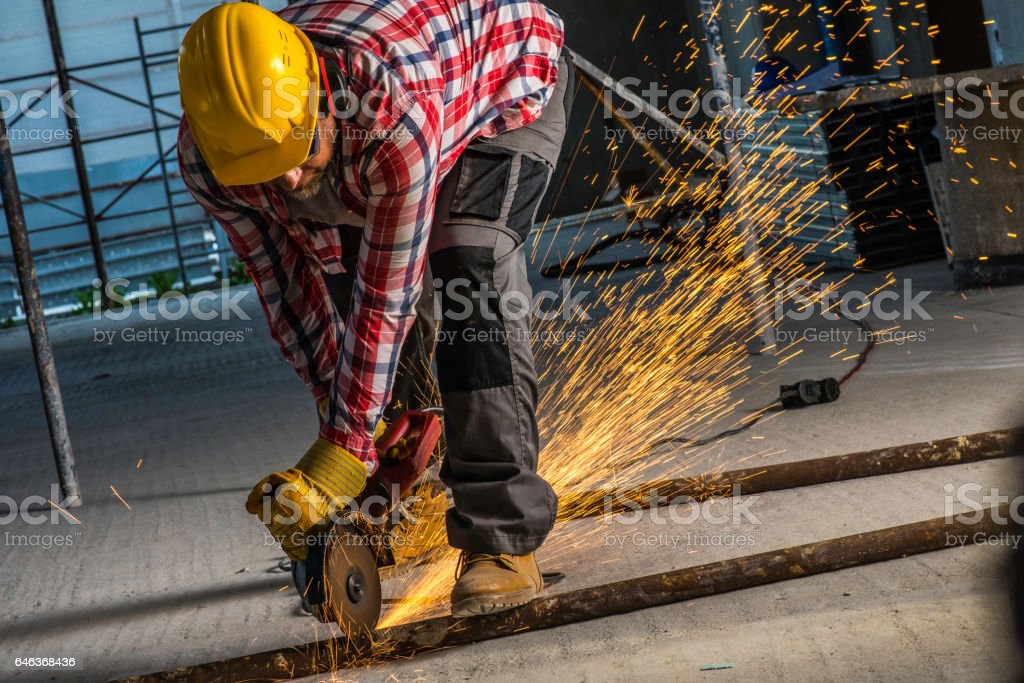 Concstruction worker cutting metal rod stock photo