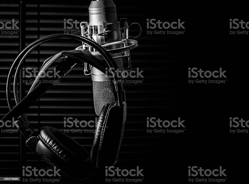 condenser microphone on boom stand with headphones, in dark studio stock photo