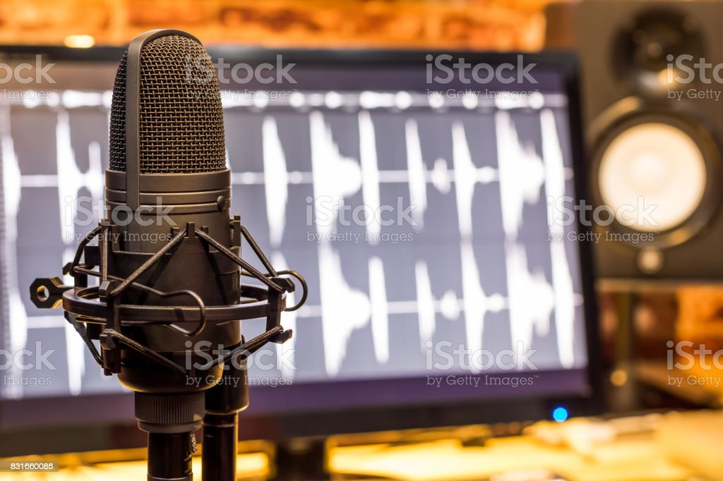 condenser microphone on computer screen showing digital wave & studio monitor speakers background, recording concept stock photo