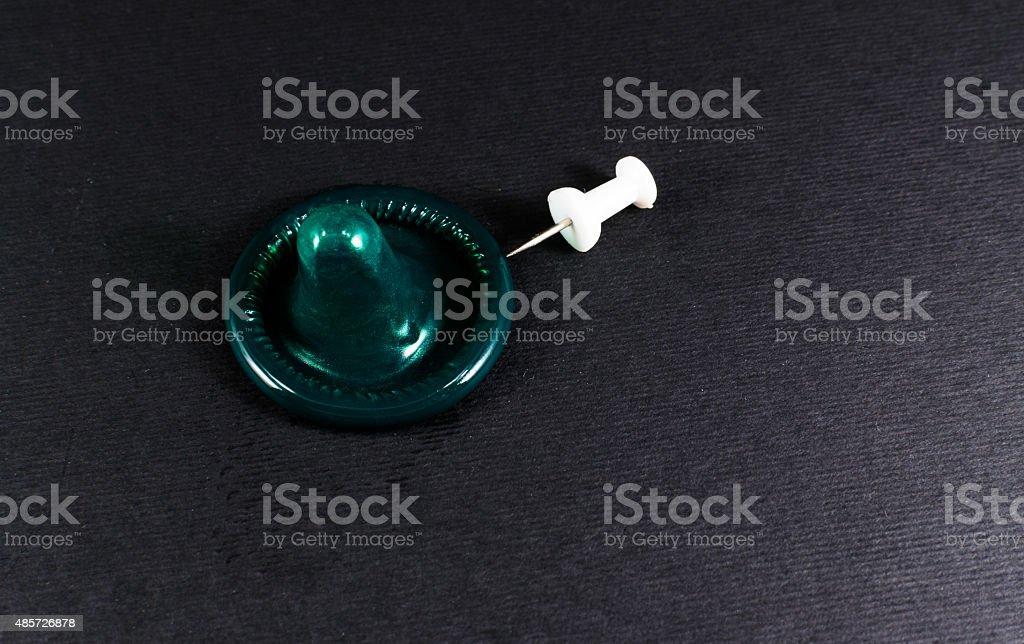 Condom and a Pin Prick stock photo